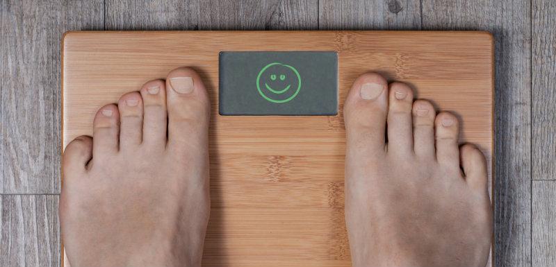Jambes de femme se tenant debout sur une balance pour vérifier son diabète de type 2