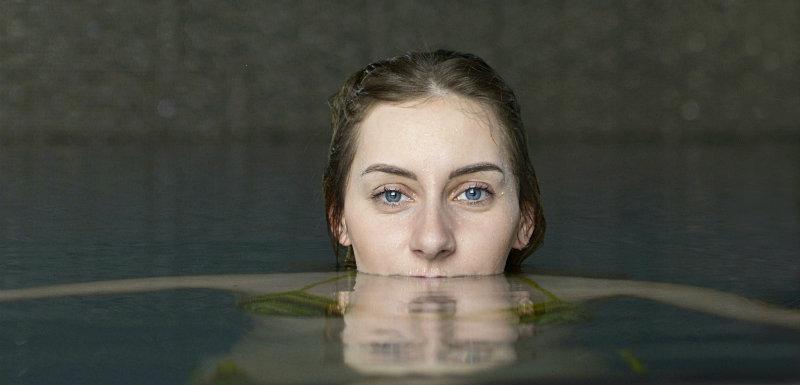 Jeune femme dans l'eau profitant des cures thermales