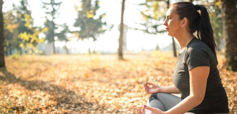 Femme en pleine foret en train de faire son yoga