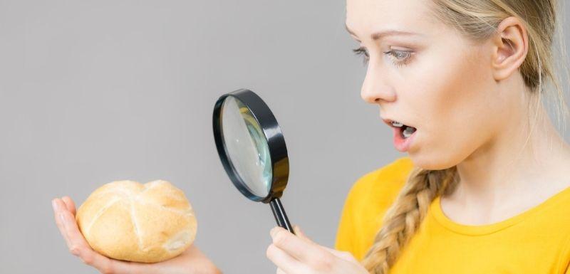 Femme observant à la loupe un pain brioché
